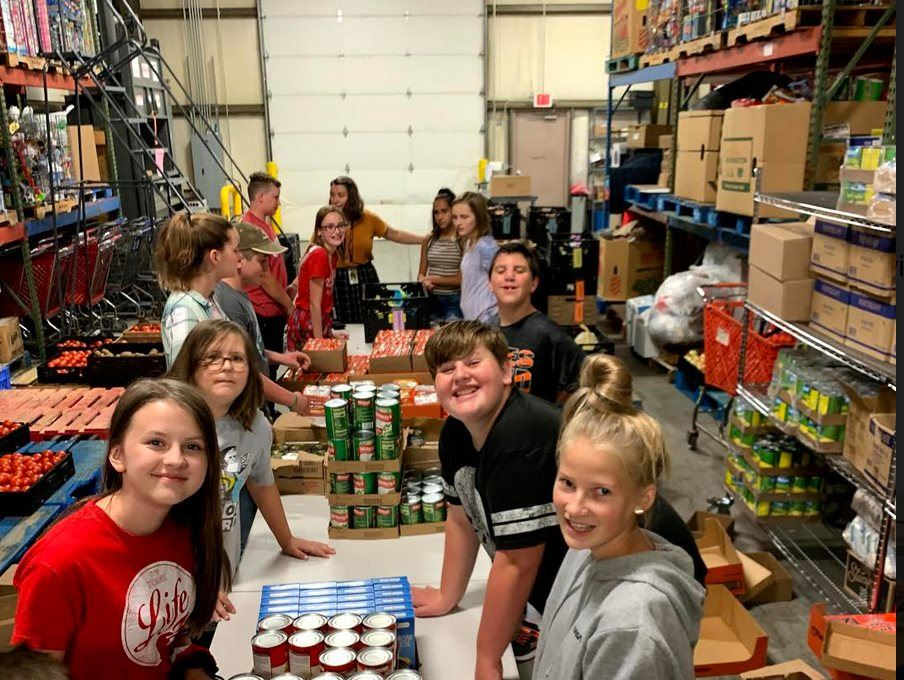 Image Description: Dempsey students help pack bags of food for the Weekend Backpack Program.